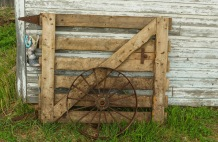 This frame shows a gate for a box stall and an old wagon wheel.